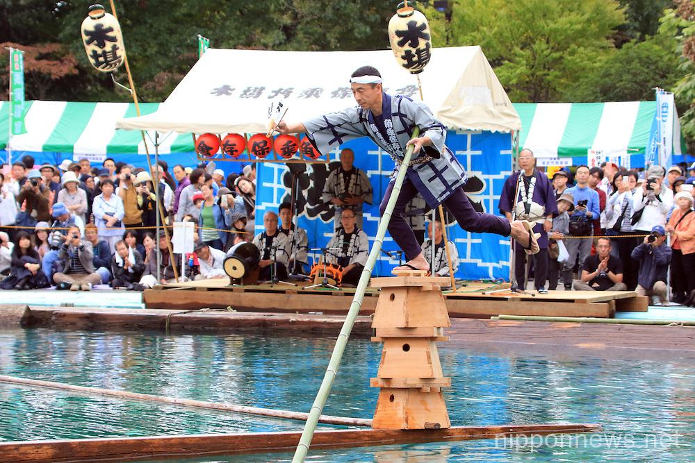 Raftsmen members of the Kiba 'kakunori' perform on wooden logs